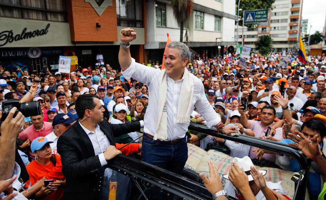 Un hombre de pie en un auto descapotable gesticula saludando a la gente que lo vitorea (© Fernando Vergara/AP Images)