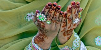 Hands decorated in henna designs raised in prayer (© K.M. Chaudary/AP Images)