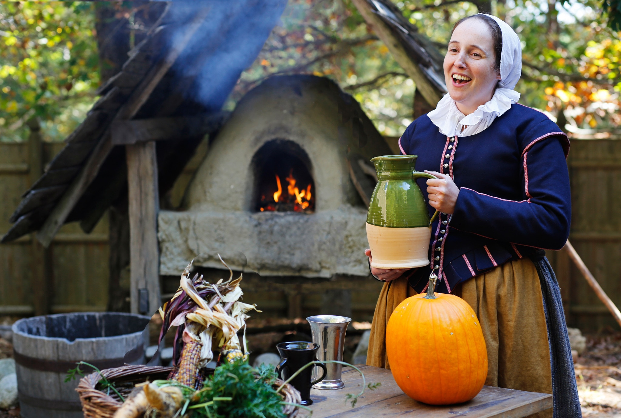 Woman in period costume holding a tankard next to a fire pit (© Plimoth Plantation)