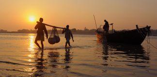 Personas cargan una bolsa desde un bote en aguas poco profundas (© Chuck Biggar/Alamy)