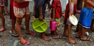 Children in a line carrying empty plates (© Jez Aznar/Getty Images)