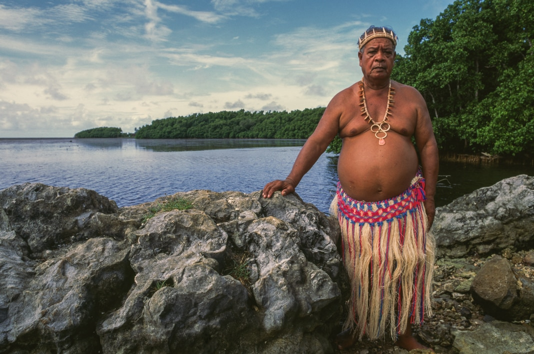 Un homme en tenue traditionnelle debout contre des roches au bord de l'eau (© Dea/V. Giannella/Getty Images)