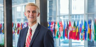 Michael Scott Peters smiling, with row of flags in the background (State Dept./D.A Peterson)