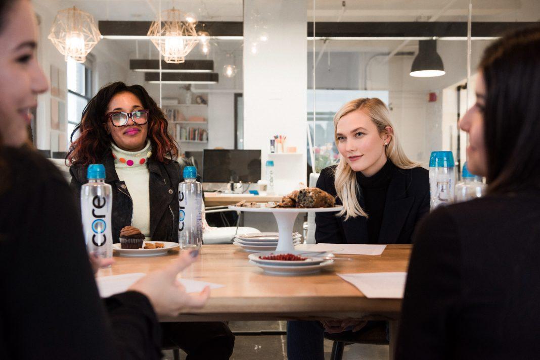 Карли Клосс с тремя молодыми женщинами у стола (© George Etheredge/The New York Times/Redux)