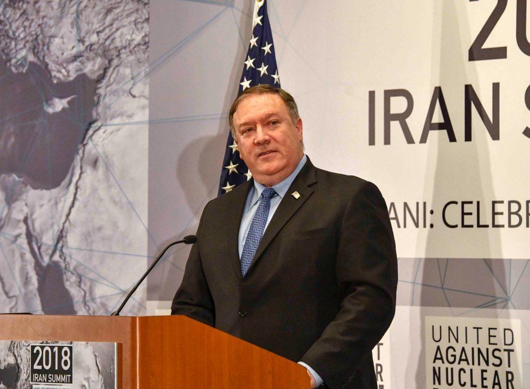 Le secrétaire d'État Mike Pompeo debout à un pupitre, un drapeau américain et une grande affiche au mur derrière lui (Département d'État)
