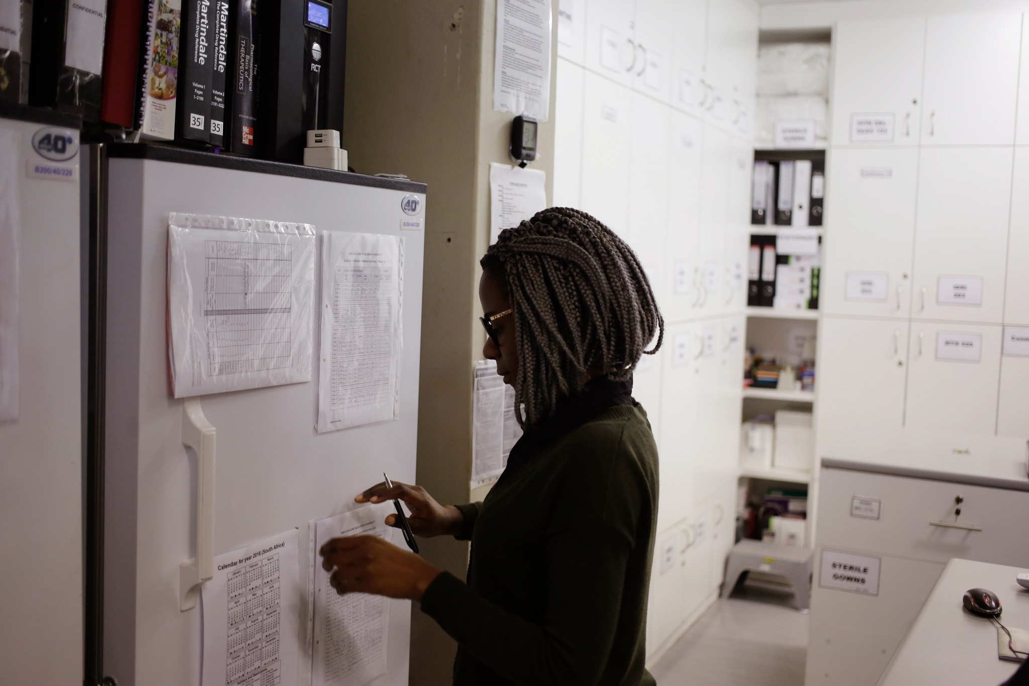 Woman looking at documents taped on a refrigerator door (© Schalk van Zuydam/AP Images)