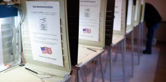 Eleitor preenche cédula no final de fileira de cabines de votação (© John Minchillo/AP Images)