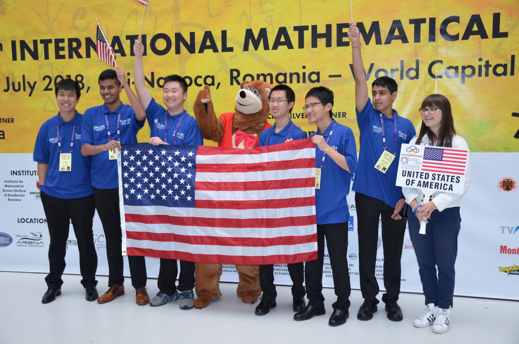 Sete pessoas e um urso mascote em pé atrás de uma bandeira americana (Associação Americana de Matemática)