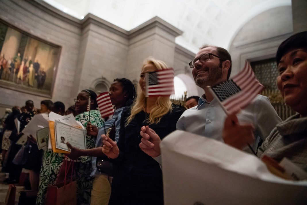 Smiling people holding small American flags (© Jim Watson/AFP/Getty Images)
