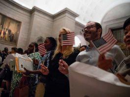 Pessoas sorridentes segurando pequenas bandeiras americanas (© Jim Watson/AFP/Getty Images)