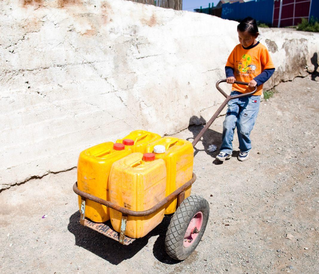 Girl pulling cart of water jugs (© Thomas Koehler/Photothek/Getty Images)