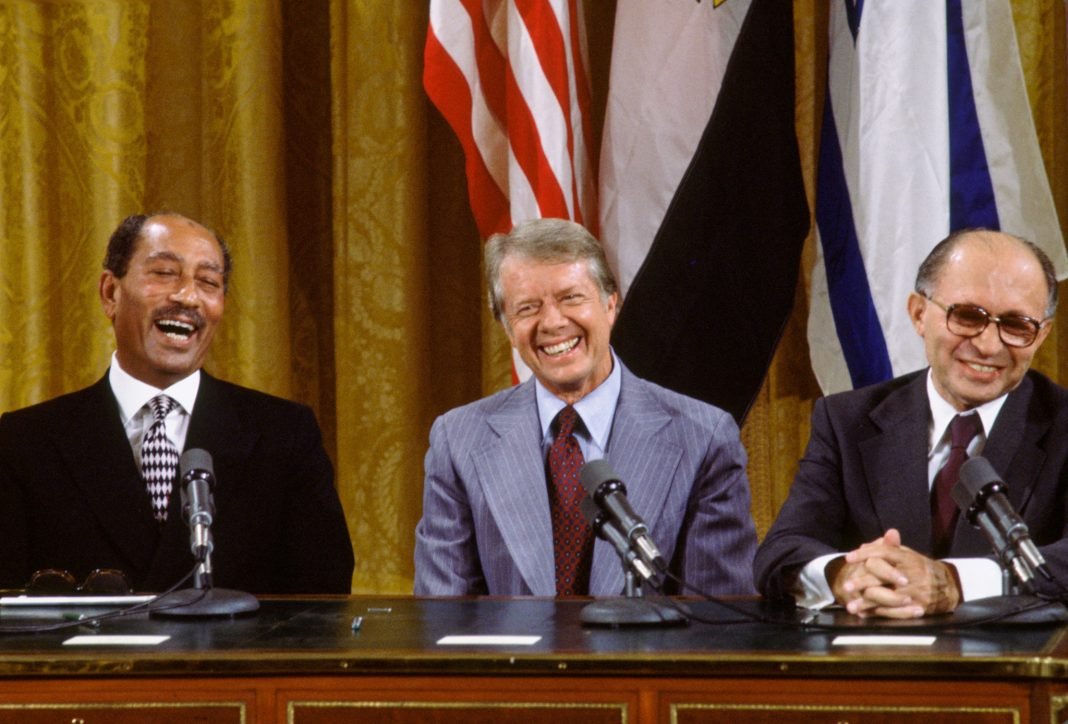 Anwar Sadat, Jimmy Carter and Menachem Begin sitting at table smiling (© David Hume Kennerly/Getty Images)