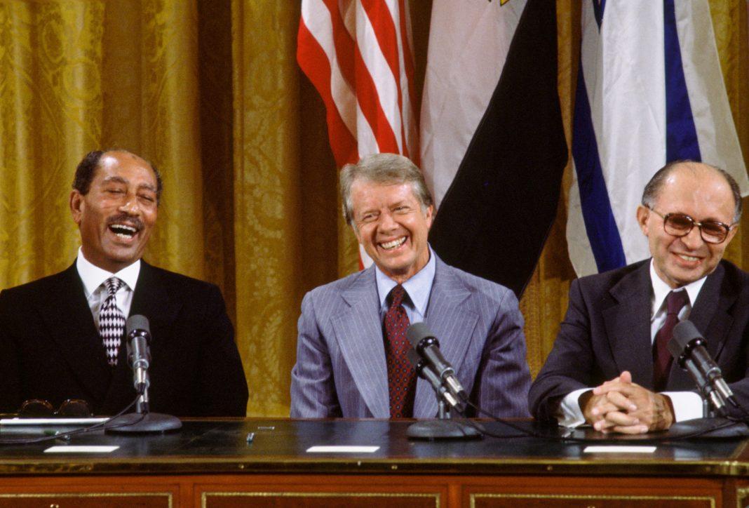 Anwar Sadat, Jimmy Carter and Menachem Begin sitting at table smiling (© David Hume Kennerly/Getty Images)