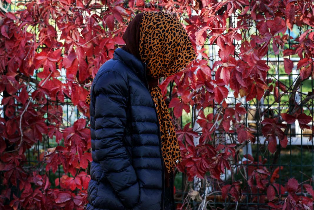 Persona con pañuelo cubriéndole la cabeza frente a una valla con hojas rojas (© Safin Hamed/AFP/Getty Images)