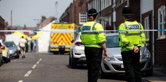 Policiais atrás de fita observando cena de crime (© Jack Taylor/Getty Images)