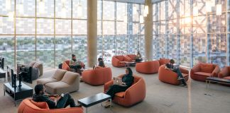Orang-orang duduk di ruangan besar dengan dinding kaca tinggi (© Northwestern University in Qatar)