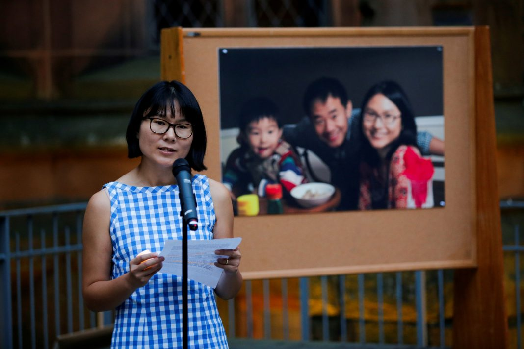Woman speaking in microphone, family portrait in background (© Eduardo Munoz/Reuters)