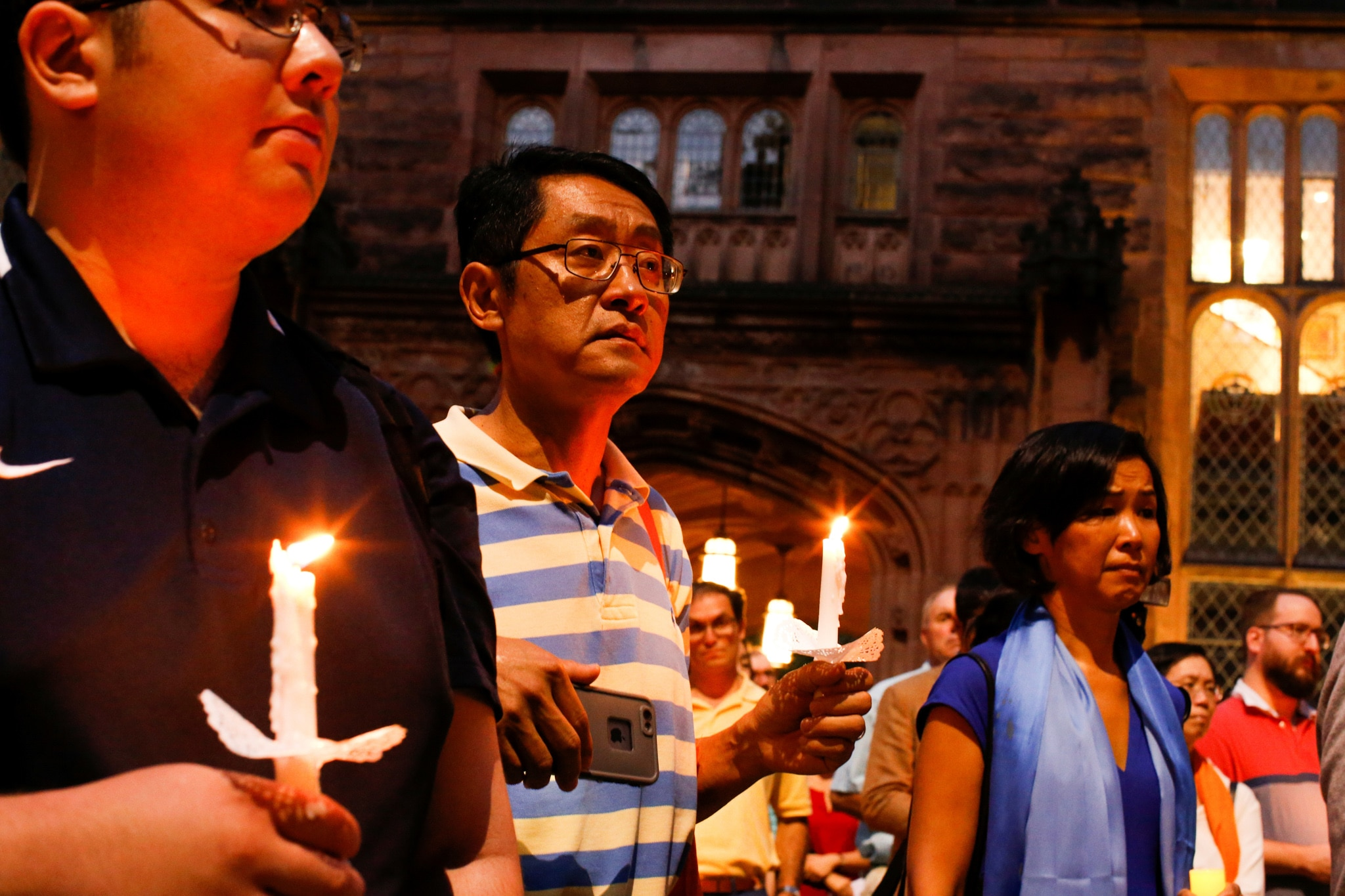 People holding candles outside building (© Eduardo Munoz/Reuters)