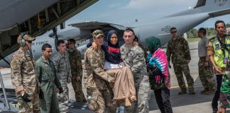 Soldiers helping people disembark a military airplane (U.S. Air Force/Master Sgt. JT May III)