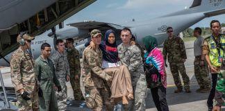 Duas pessoas em uniforme de camuflagem carregam mulher enquanto outras pessoas permanecem de pé perto de aviões militares (Força Aérea dos EUA/Primeiro-sargento JT Maio III)