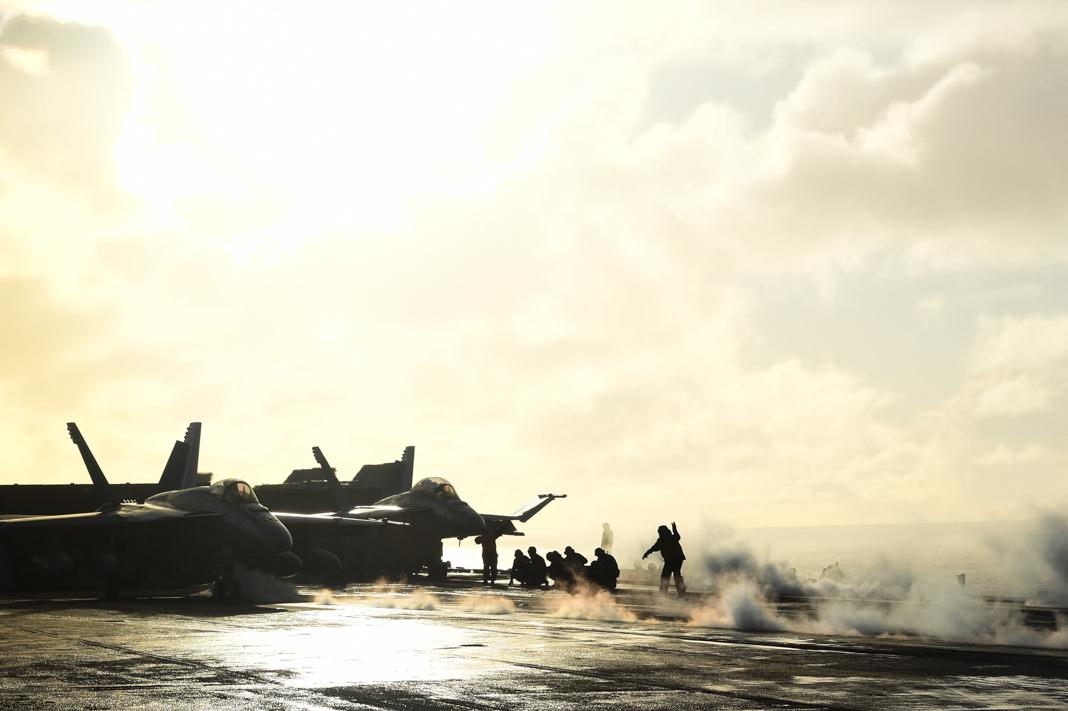 رجال يقتربون من طائرات مقاتلة في صباح يغمره ضوء الشمس الساطع ويتخلله الضباب (U.S. Navy/Mass Communication Specialist Adelola Tinubu)