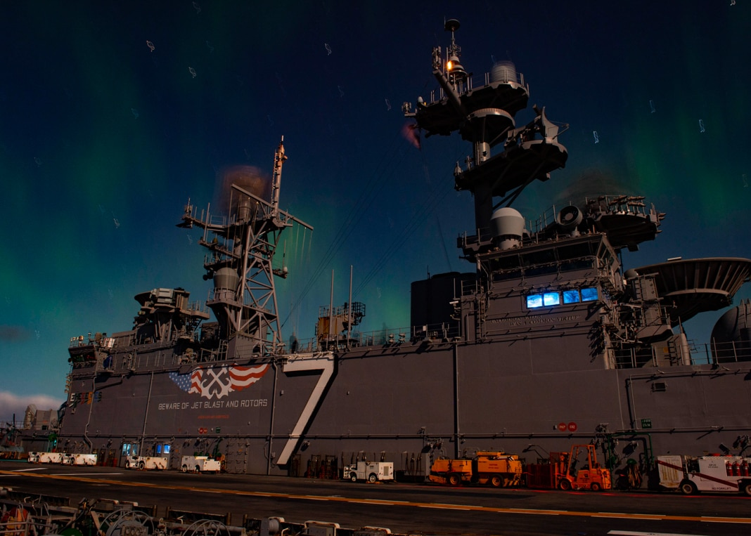 سفينة عسكرية في الليل تحيط بها أضواء الشفق القطبي الشمالي (U.S. Navy/Mass Communication Specialist Kevin Leitner)