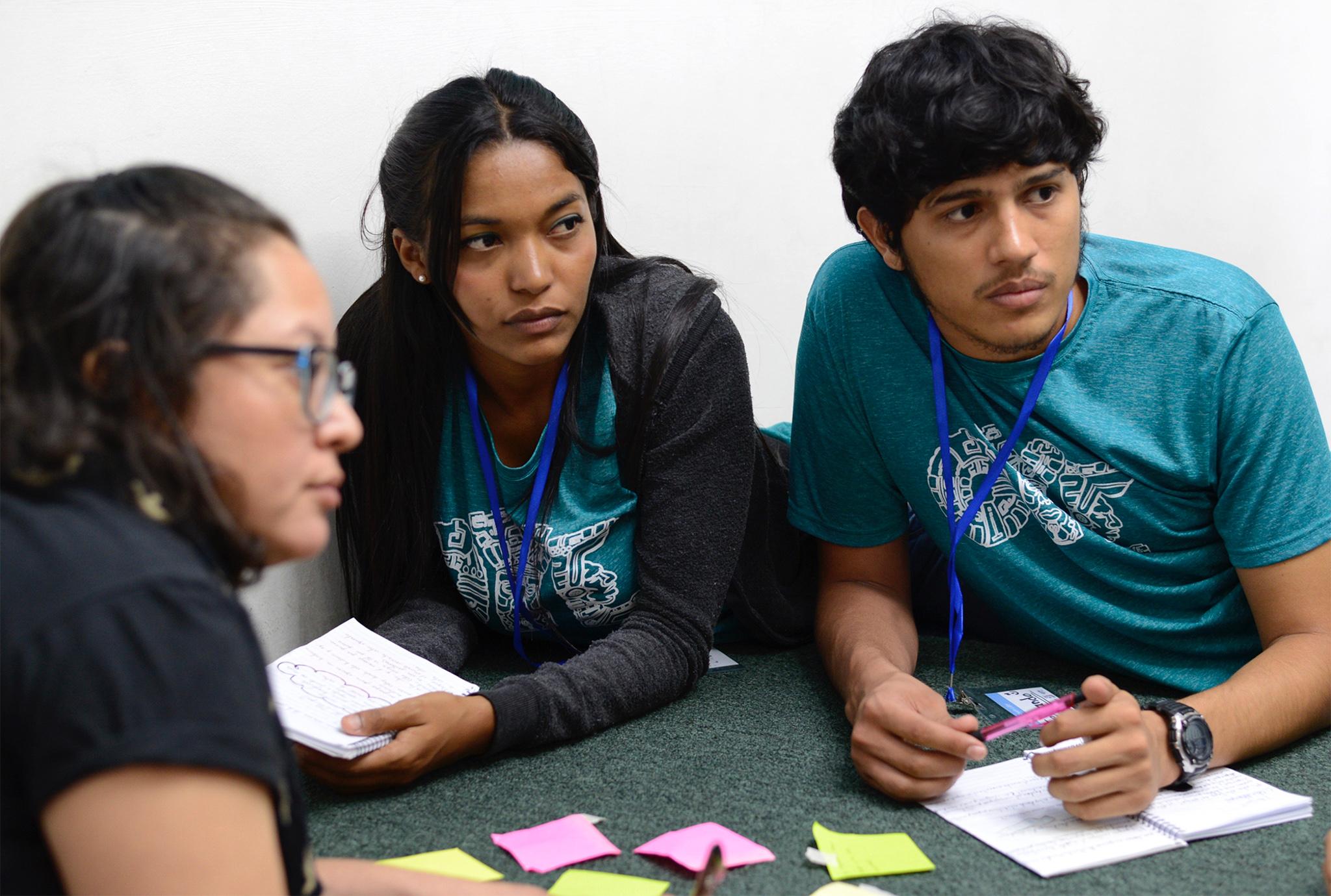 Three seminar participants listening and writing ideas (U.S. Embassy of Tegucigalpa)