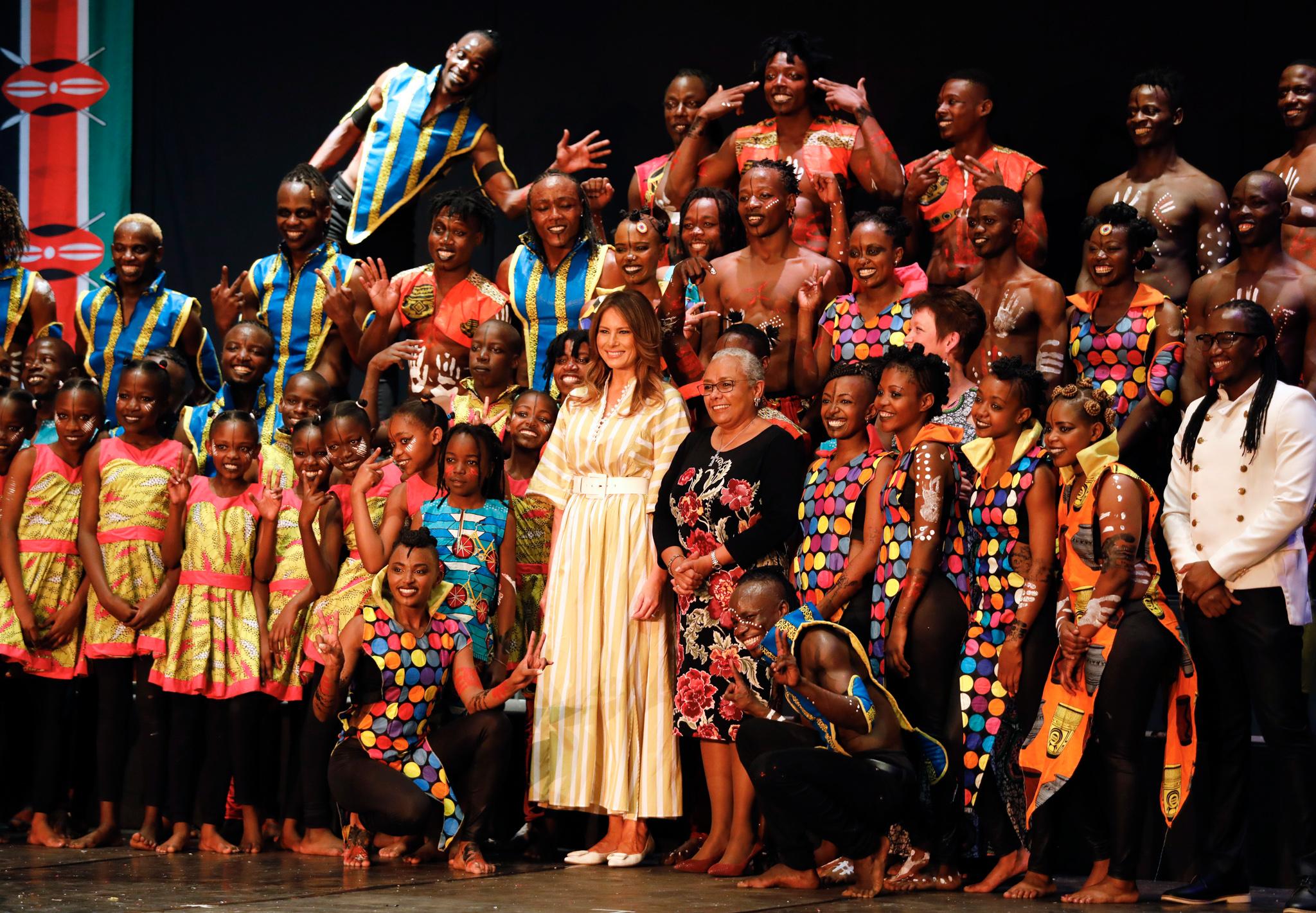 Melania Trump e Margaret Kenyatta em pé com dançarinos fantasiados (© Dai Kurokawa/AP Images)