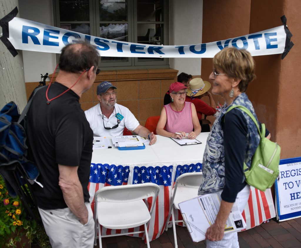 People standing and sitting near table and banner reading 'Register to vote' (© Robert Alexander/Getty Images)
