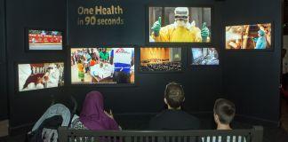 Trois personnes assises sur un banc regardant plusieurs écrans de TV accrochés sur un mur (D.A. Peterson/Département d'État)