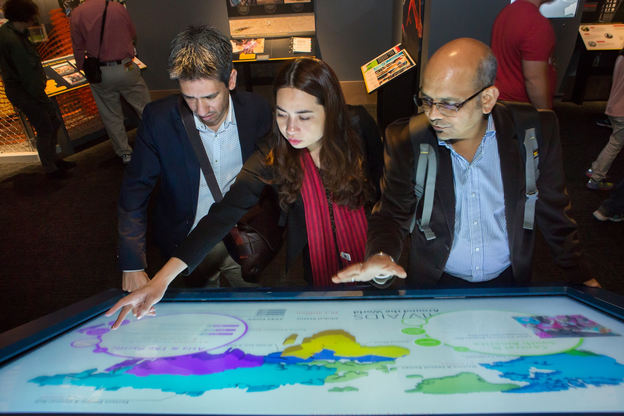 Two men and a woman leaning over an interactive map (D.A. Peterson/State Dept)