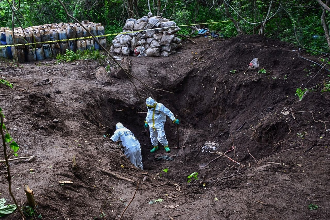 Two people wearing white protective suits in large pit (© SEMAR Mexico Navy/Reuters)
