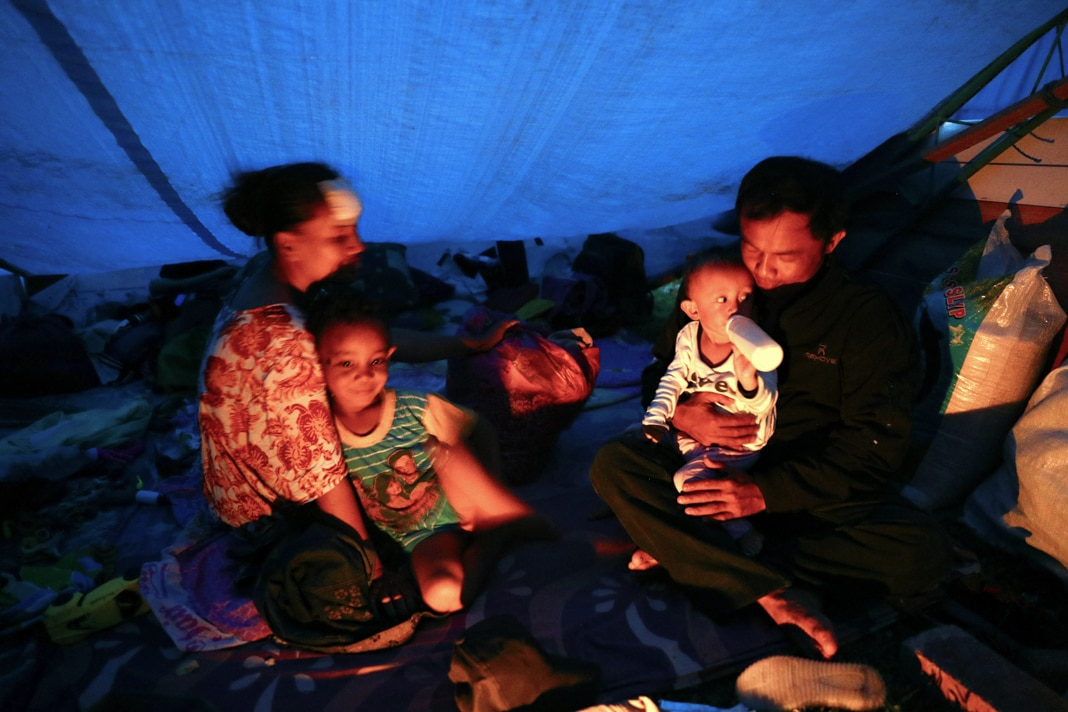 Orang duduk di tenda. © Athit Perawongmetha/Reuters)