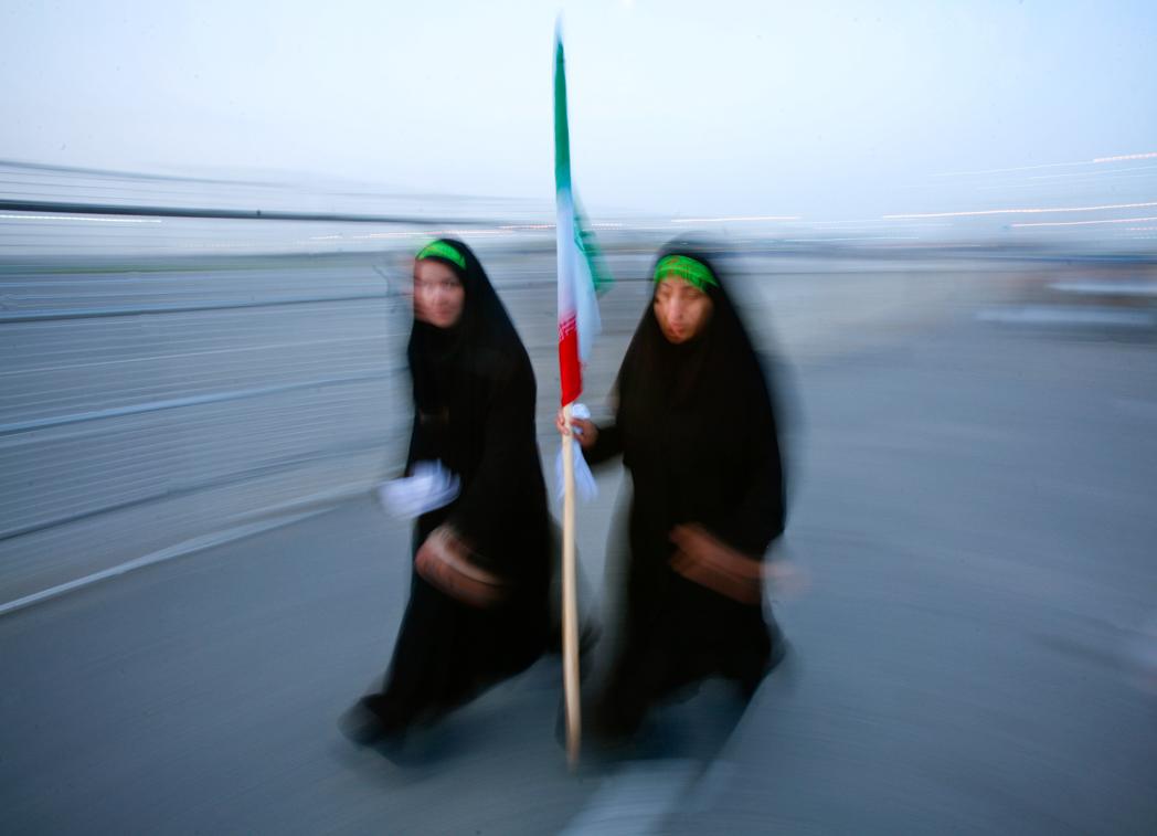 Dos mujeres caminando, una sostiene una bandera (© Morteza Nikoubazl/Reuters)