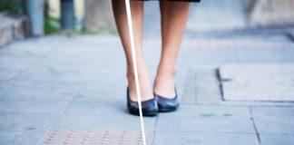 Les jambes d'une femme sur un trottoir, utilisant une canne blanche (Shutterstock)