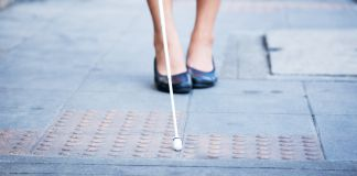 Blind woman walking on the sidewalk, using a white cane (© Shutterstock)