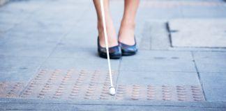 Blind woman walking on the sidewalk, using a white cane (© Shutterstock)