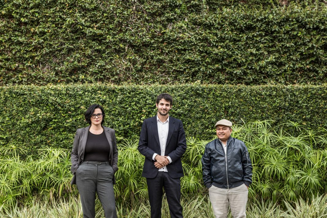 Three people standing in front of hedge (© Emily Berl/State Dept.)