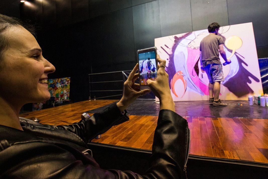 Une femme en train de prendre en photo un homme peignant un mur (Diego Astarita/AmCham)