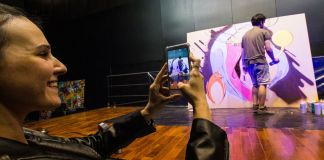 Woman taking a picture with her cellphone of a man spray painting a mural (Diego Astarita/AmCham)