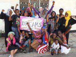 Grupo de meninas posando com cartaz da iniciativa Dreams (© Sauti)