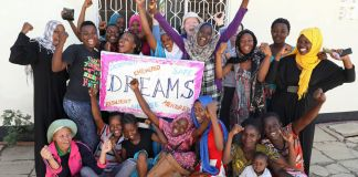 Group of girls posing with DREAMS sign (© Sauti)