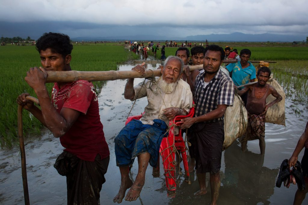 Line of people walking along river, carrying people and belongings (© Bernat Armangue/AP Images)