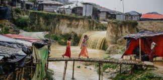 Niñas de una barriada caminando en un puente precario sobre una quebrada (© Altaf Qadri/AP Images)