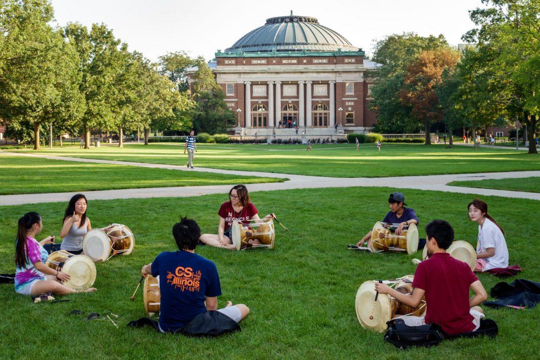 Des jeunes assis en cercle sur une pelouse, en train de jouer du tambour, avec un bâtiment à l'arrière-plan (© RosaIreneBetancourt 7/Alamy)