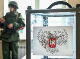 Military personnel standing behind ballot box (© Mikhail Tereshchenko/TASS/Getty Images)