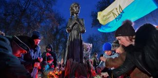 People laying offerings at base of statue (© Genya Savilov/AFP/Getty Images)
