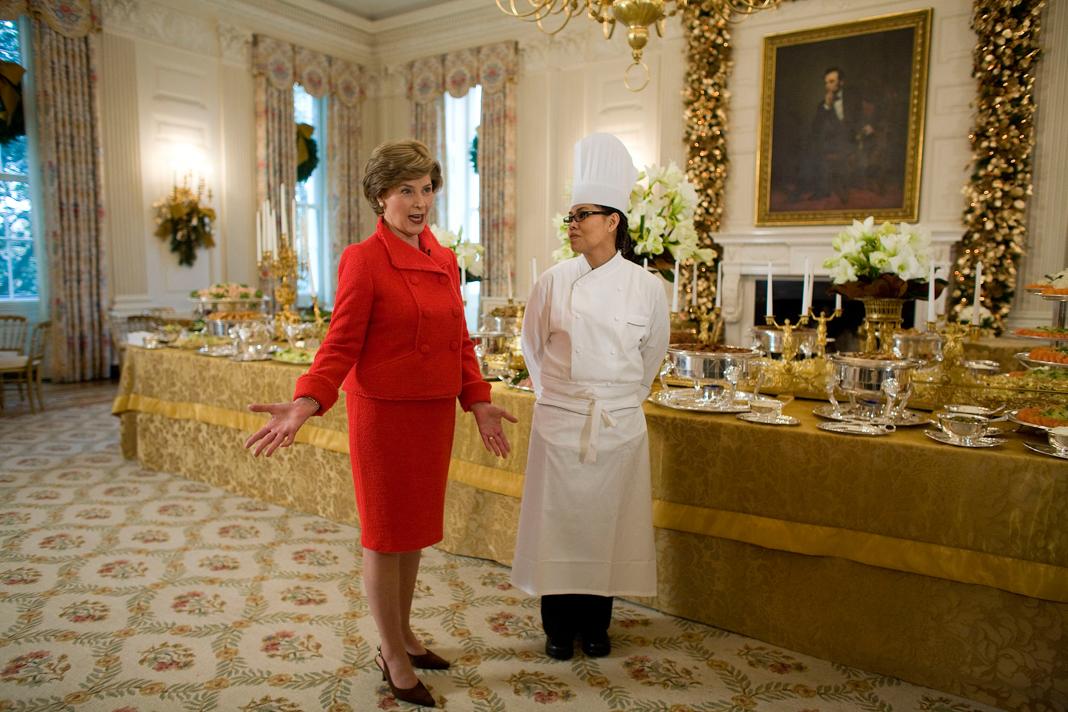 Laura Bush y Cristeta Comerford en el comedor de la Casa Blanca, cerca de una mesa larga decorada (© Chuck Kennedy/MCT/Getty Images)