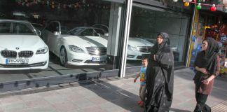 People walking past car dealership window (© Franco Czerny/Getty Images)