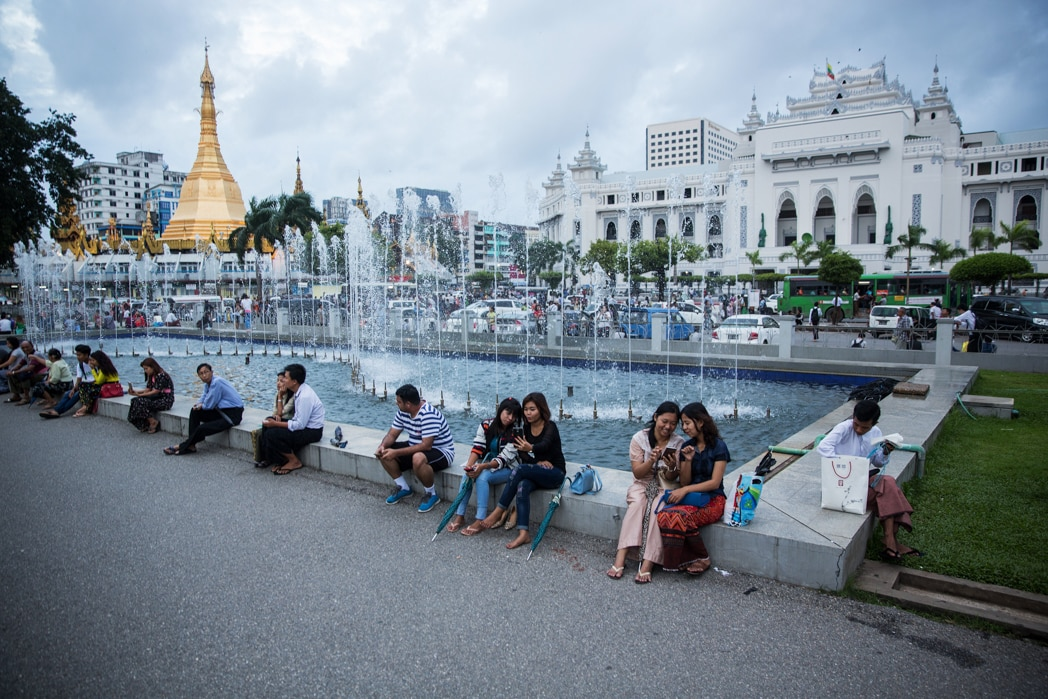 Orang-orang duduk di samping air mancur dan melihat ponsel (© Taylor Weidman/Bloomberg/Getty Images)